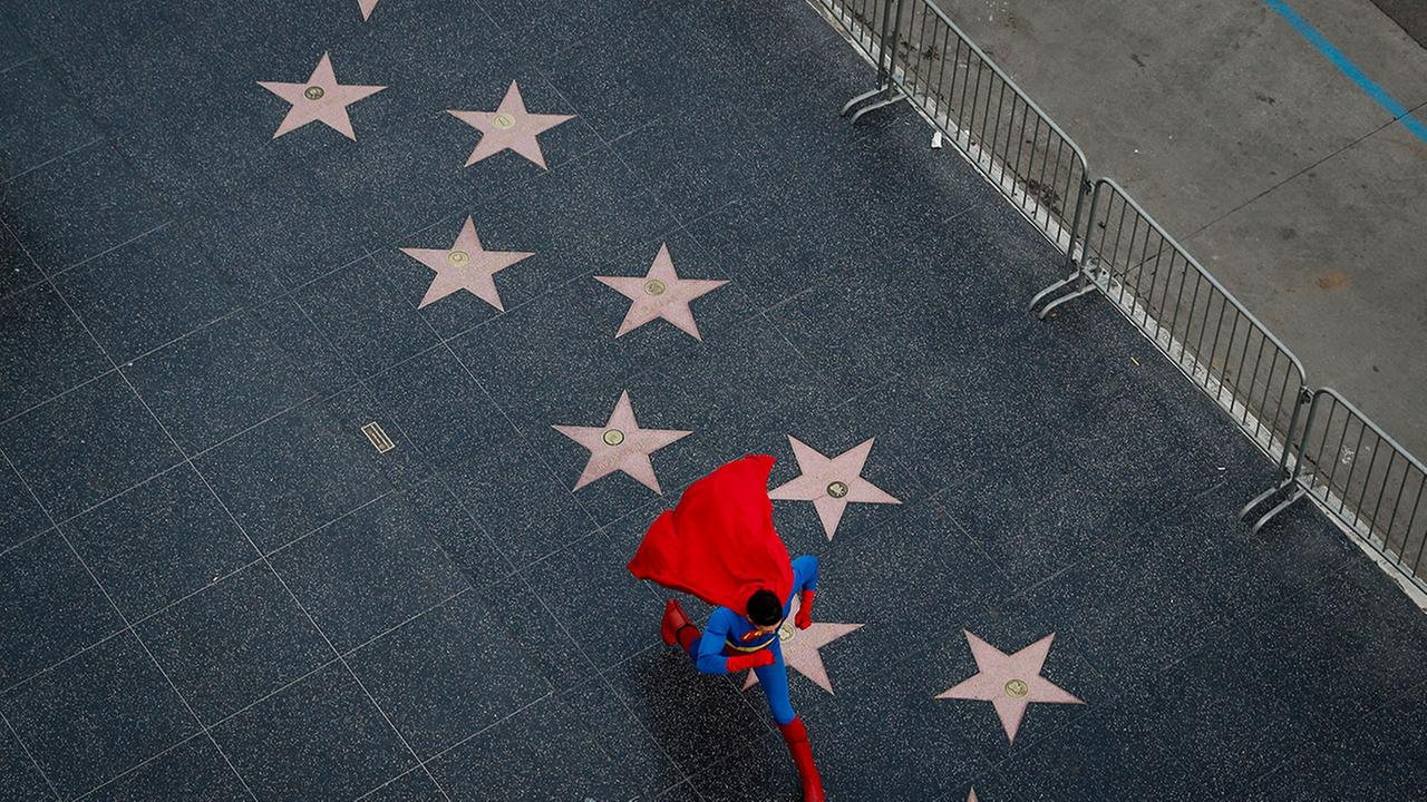 In this Thursday, March 2, 2017 photo, wearing a Superman costume, Toly Shtapenko, of Ukraine, takes a long stride along the Hollywood Walk of Fame to impress tourists.Jae C. Hong