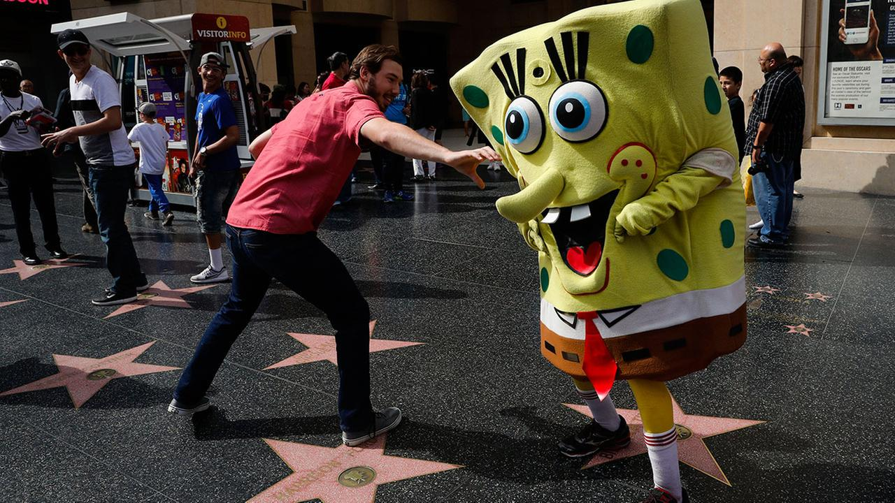 In this Monday, April 17, 2017 photo, Belnarr Golden, wearing a SpongeBob SquarePants costume, dodges a tourist trying to pull the nose of his costume on Hollywood Boulevard.Jae C. Hong
