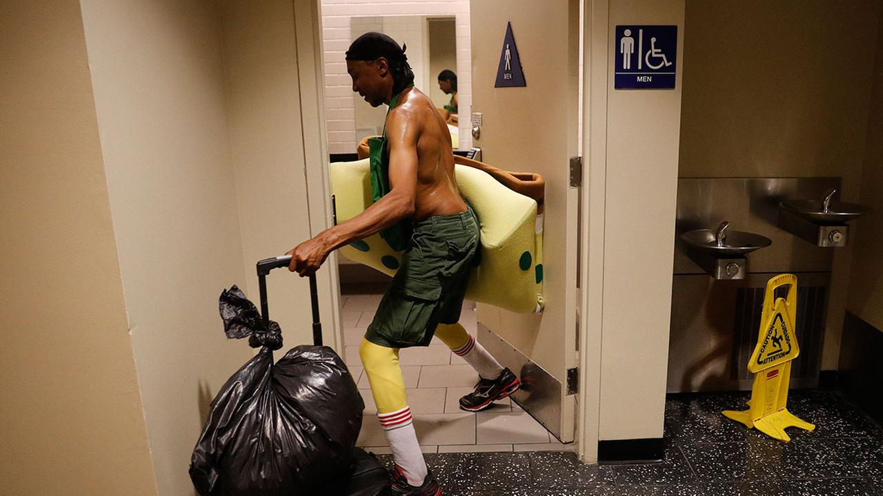 In this Monday, April 17, 2017 photo, covered in sweat, impersonator Belnarr Golden enters a public restroom with his SpongeBob SquarePants costume after working on Hollywood Blvd.Jae C. Hong