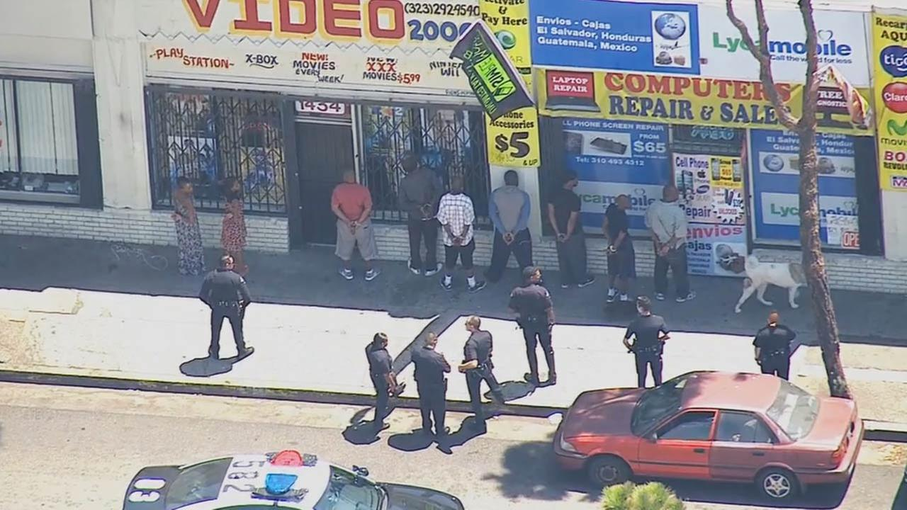 LAPD officers are searching for a suspect in South Los Angeles reportedly carrying a shotgun that fell from a police motorcycle on Thursday, July 31, 2014.