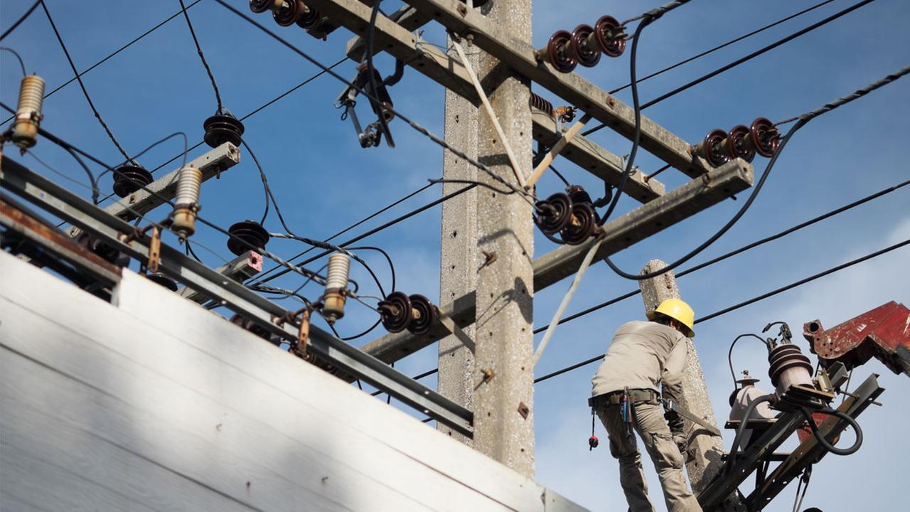 An electrical crew worker fixes or repairs a broken power line in a stock photo.