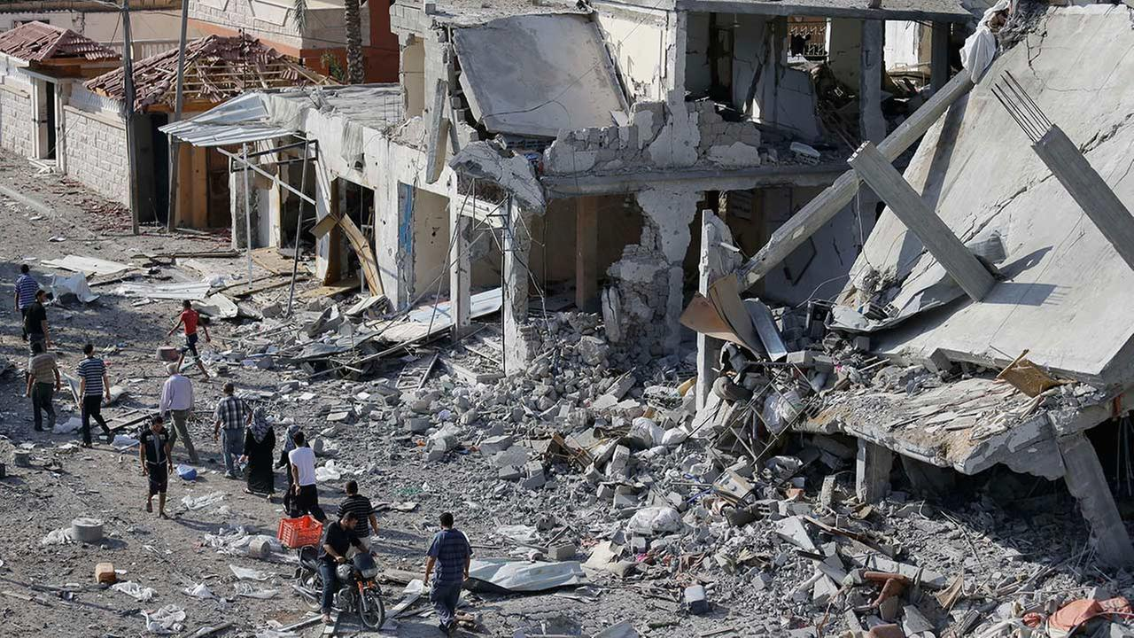 Palestinians walk by the rubble of destroyed houses in the heavily bombed town of Beit Hanoun, Gaza Strip, close to the Israeli border, Friday, Aug. 1, 2014.
