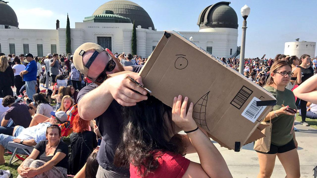 Eclipse fans at Griffith Park use a box to view the total solar eclipse on Monday, Aug. 21, 2017.