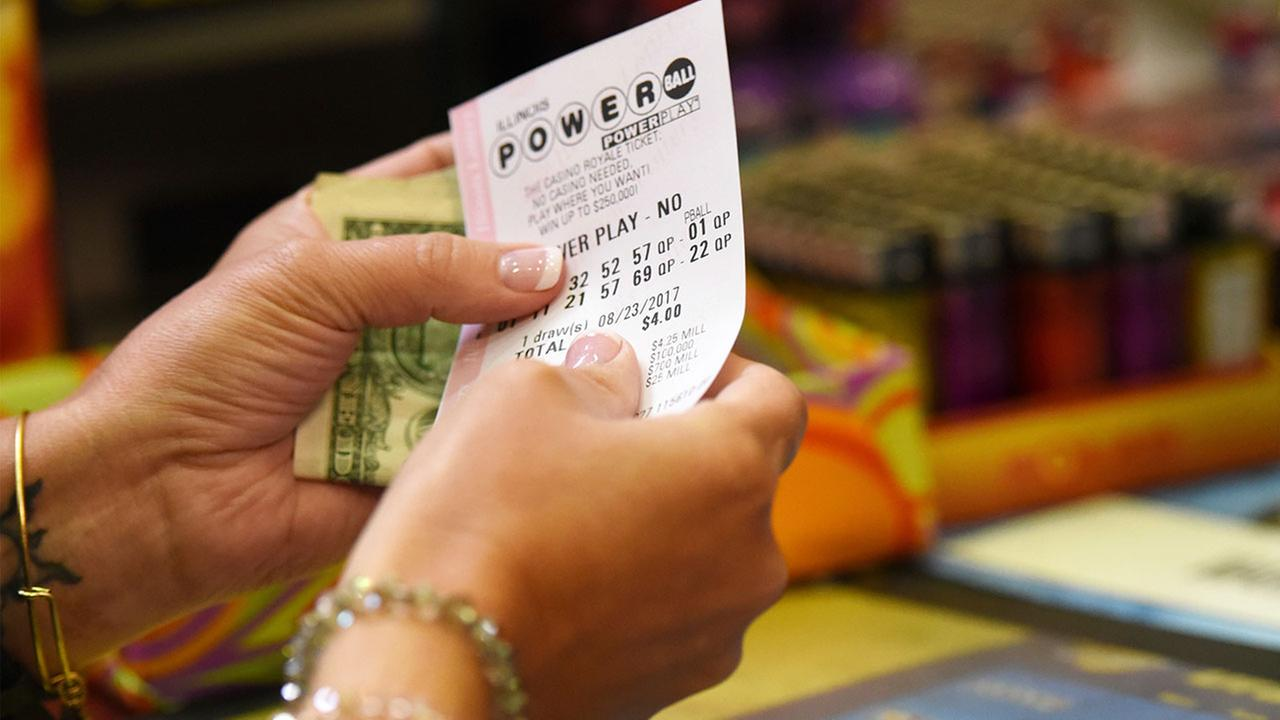 FILE - Customer buys a Powerball ticket, Tuesday, Aug. 22, 2017, in Chicago.