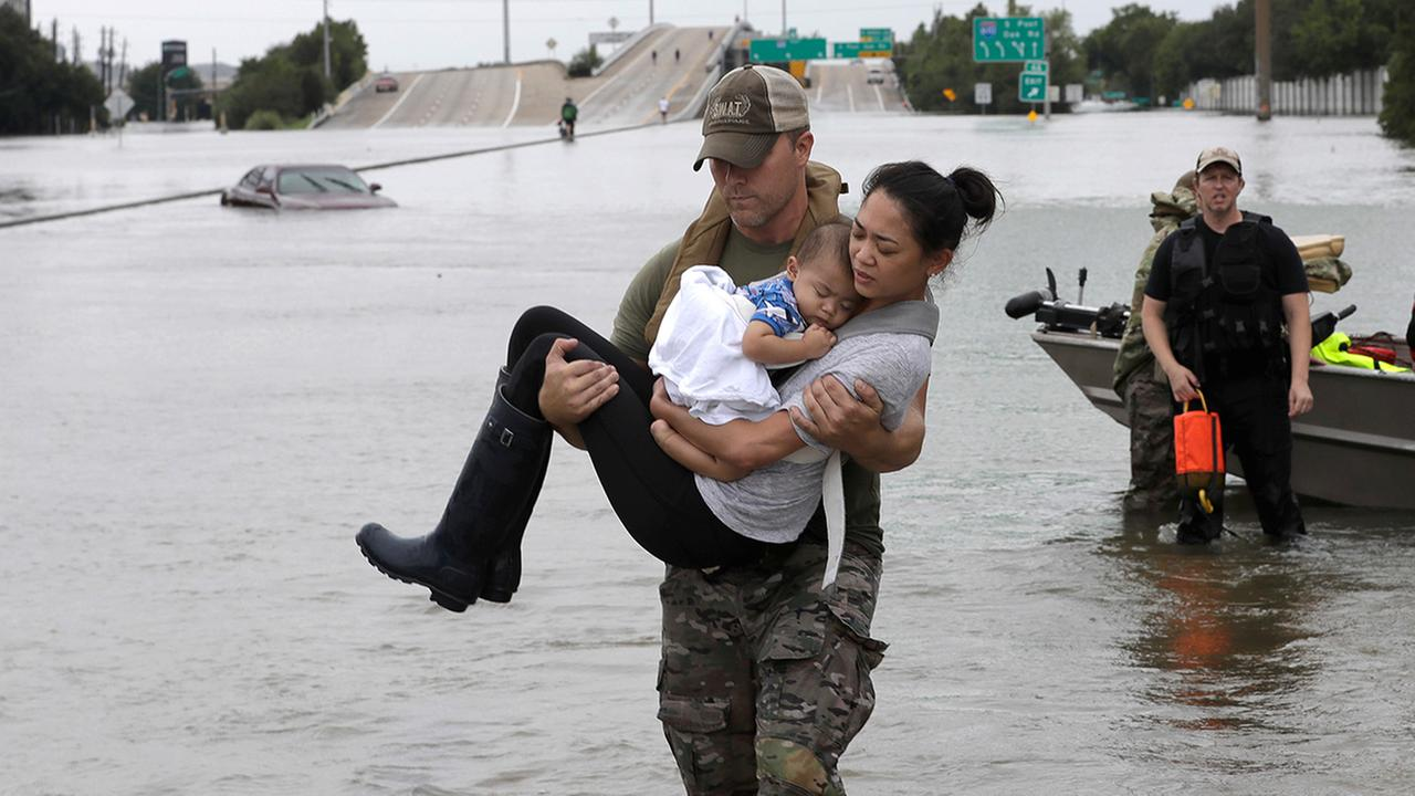 Houston Police SWAT officer Daryl Hudeck carries Catherine Pham and her son Aiden after rescuing them from their home surrounded by floodwaters from Tropical Storm Harvey.