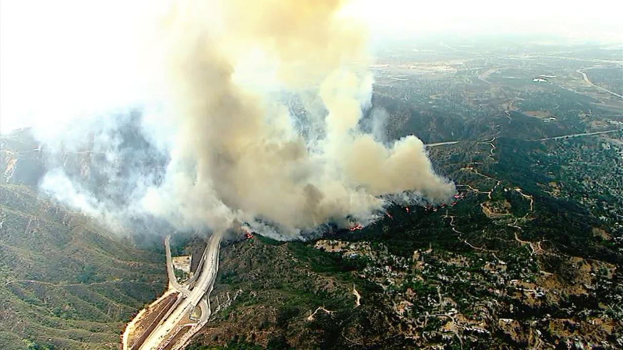 Heavy smoke is rising high above Sun Valley from a brush fire along the 210 Freeway.