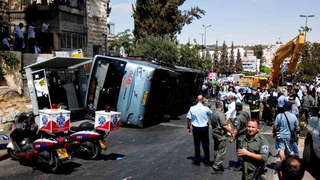 Israelis stand near a flipped bus at the scene of an attack in Jerusalem, Monday, Aug. 4, 2014.