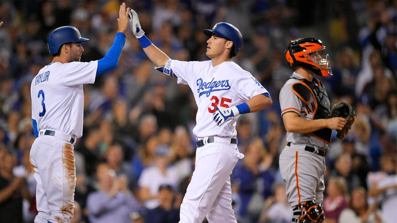 Los Angeles Dodgers Cody Bellinger, center, is congratulated by Chris Taylor, left, after hitting a three-run home run.