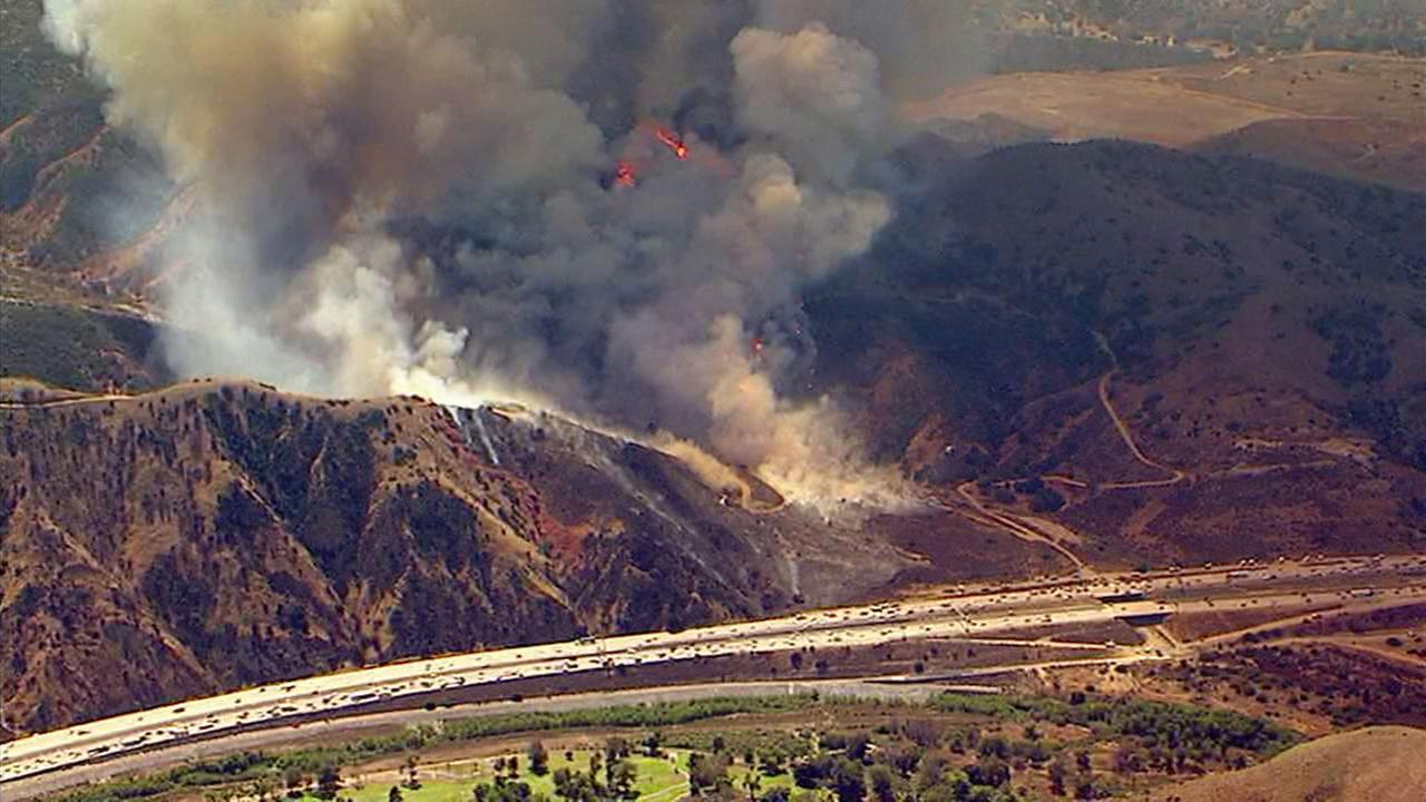 A brush fire seen burning along the 91 Freeway near the border of Anaheim and Corona on Monday, Sept. 25, 2017.