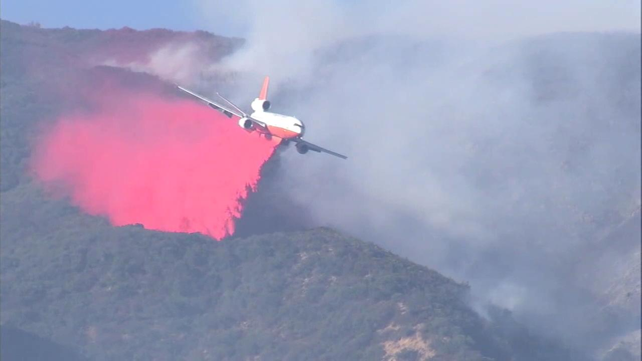 An aircraft drops fire retardant on the Canyon Fire on Monday, Sept. 25, 2017.
