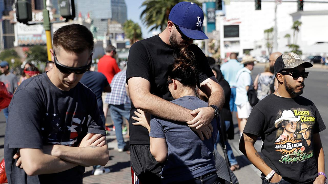 Reed Broschart, center, hugs his girlfriend Aria James on the Las Vegas Strip in the aftermath of a mass shooting at a concert Monday, Oct. 2, 2017, in Las Vegas.
