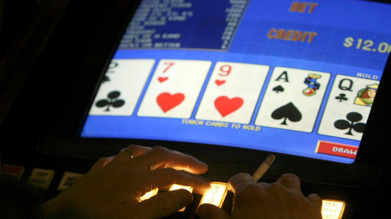In this Feb. 17, 2005 file photo, an unidentified man plays video poker at the Carson Station in Carson City, Nev.