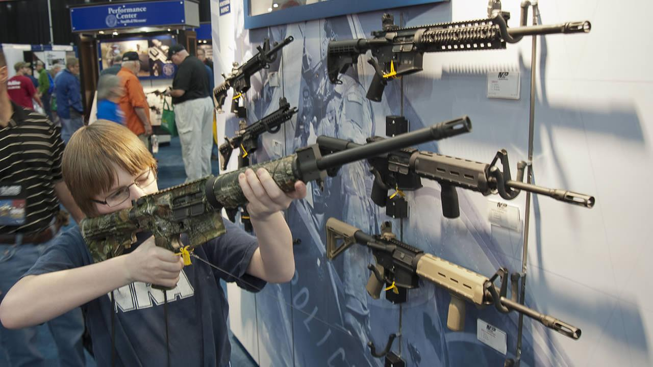 A young man who chose not to give his name sizes-up an assault style rifle during the National Rifle Associations annual convention on May 3, 2013 in Houston. (AP Photo/Steve Ueckert)