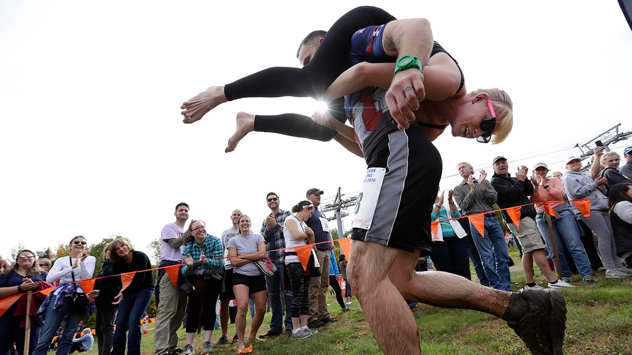 In this Oct. 8, 2016 file photo, Jaime Devine is carried by her husband, Thomas Devine, of Boston, Mass., during the North American Wife Carrying Championship at the Sunday River Ski Resort in Newry, Maine.