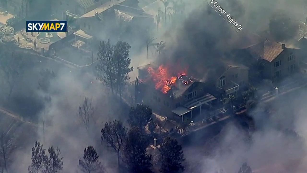 Homes could be seen burning after a brush fire spread along the 91 Freeway Monday.