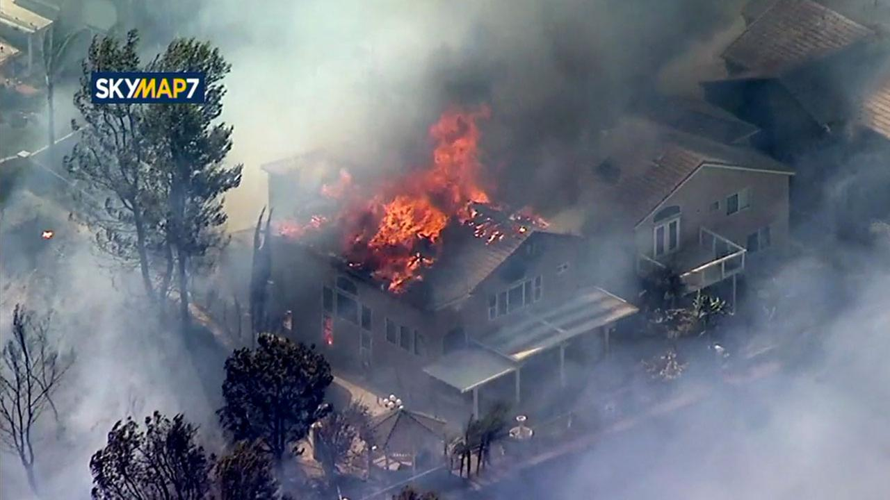 A home caught fire Monday in an Anaheim Hills neighborhood, one of several that burned due to a brush fire.