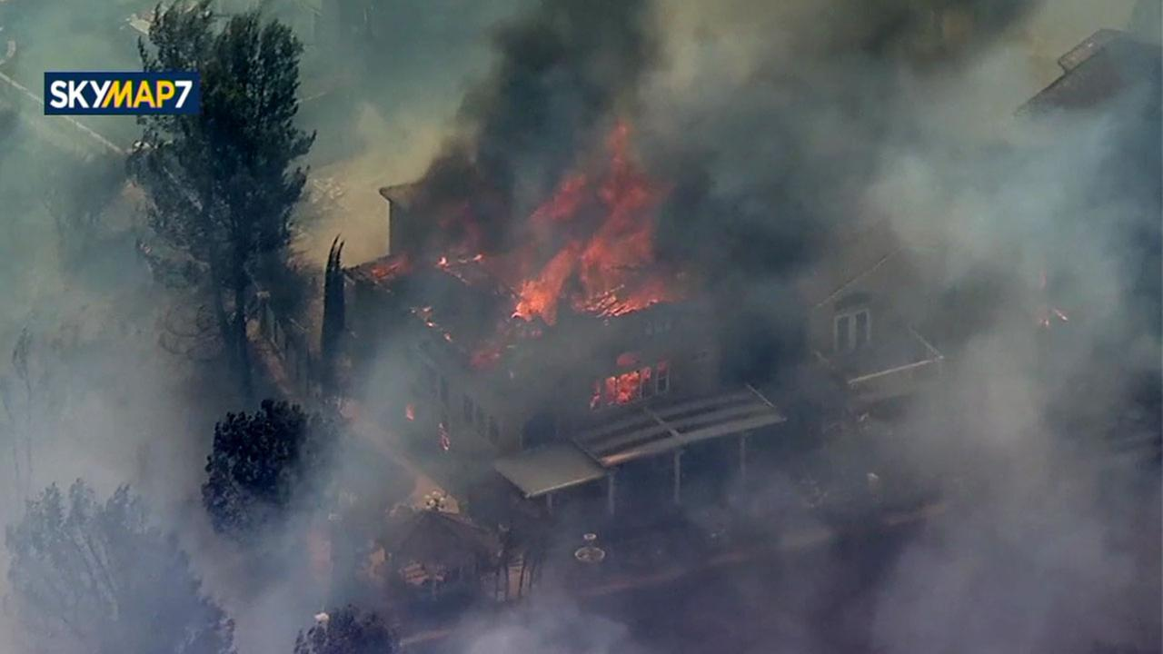 Homes burned in an Anaheim Hills neighborhood Monday after a quick-moving brush fire spread.