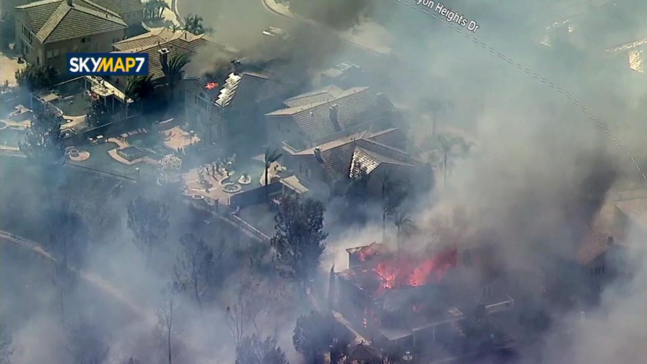 Multiple homes could be seen engulfed in flames in an Anaheim Hills neighborhood after a brush fire spread Monday.