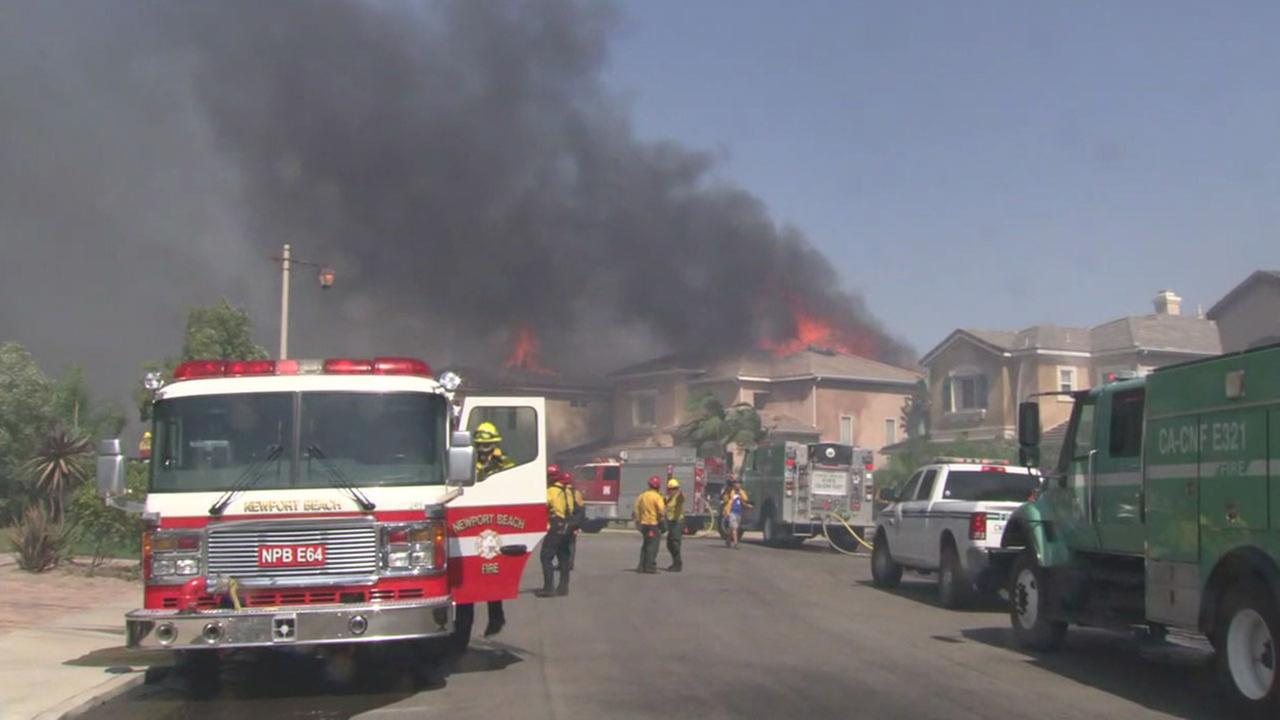 Firefighters were working to protect homes in Anaheim Hills as a brush fire spread through the neighborhood.