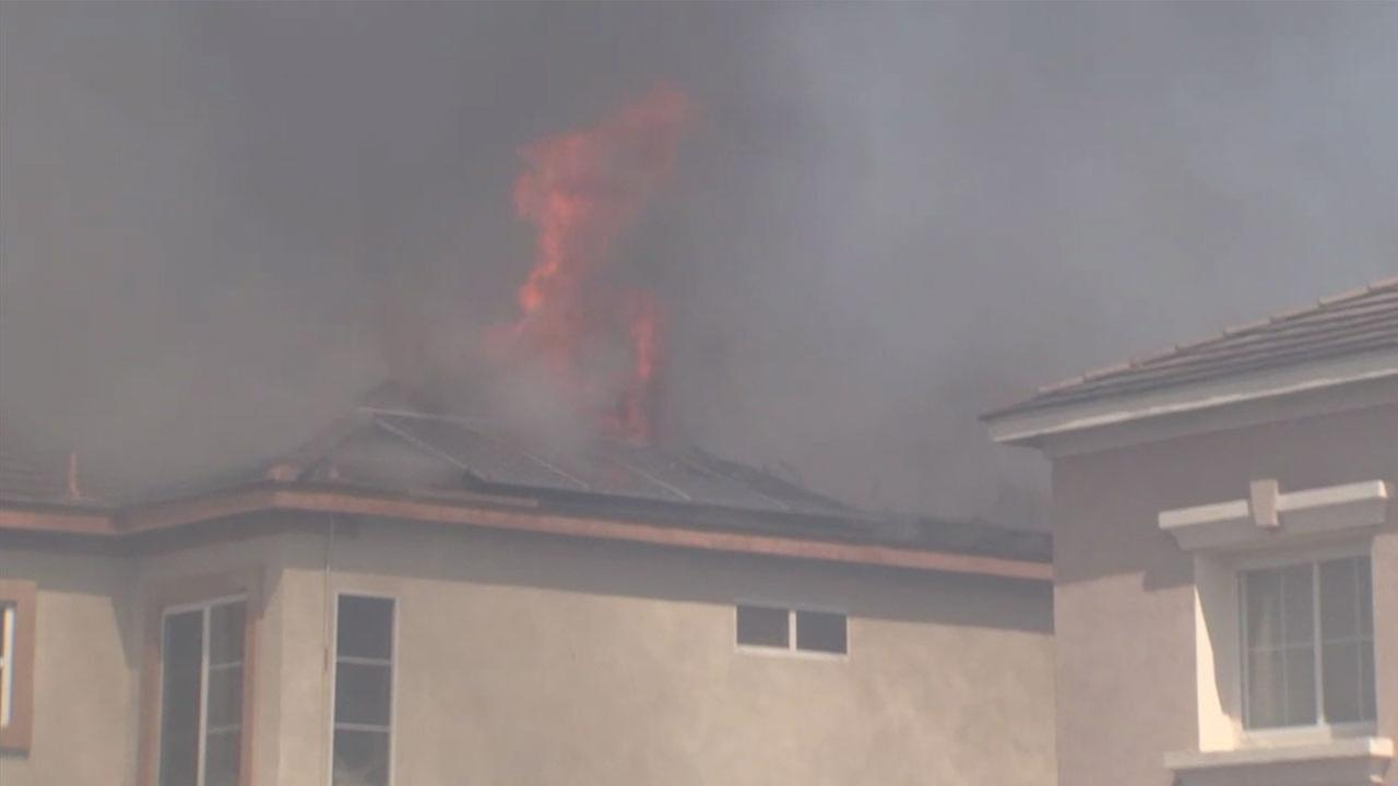 The roof of a home caught fire Monday as a fast-moving brush fire spread into a neighborhood in Anaheim Hills.