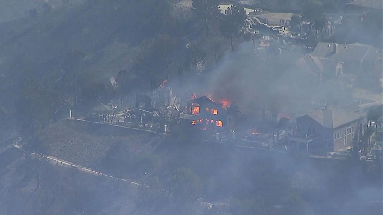 A home was completely destroyed in a brush fire that burned into an Anaheim Hills neighborhood Monday. Several houses caught fire.