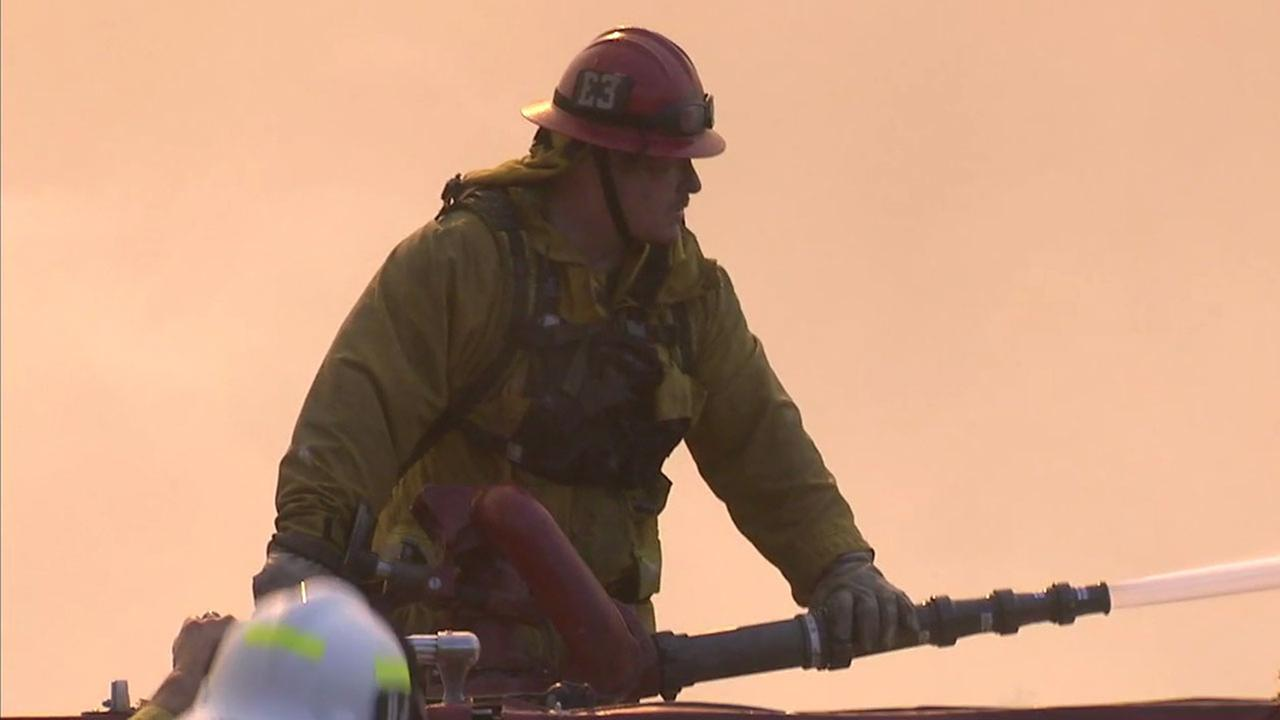 A firefighter aimed a hose at flames from the Canyon Fire 2 burning near Anaheim Hills. More than 500 firefighters were battling the blaze Monday.