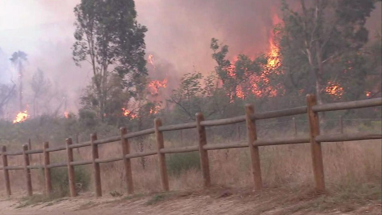 Flames burned near pastures and horse stables in the Anaheim and Orange areas as residents rushed to evacuate their animals Monday.