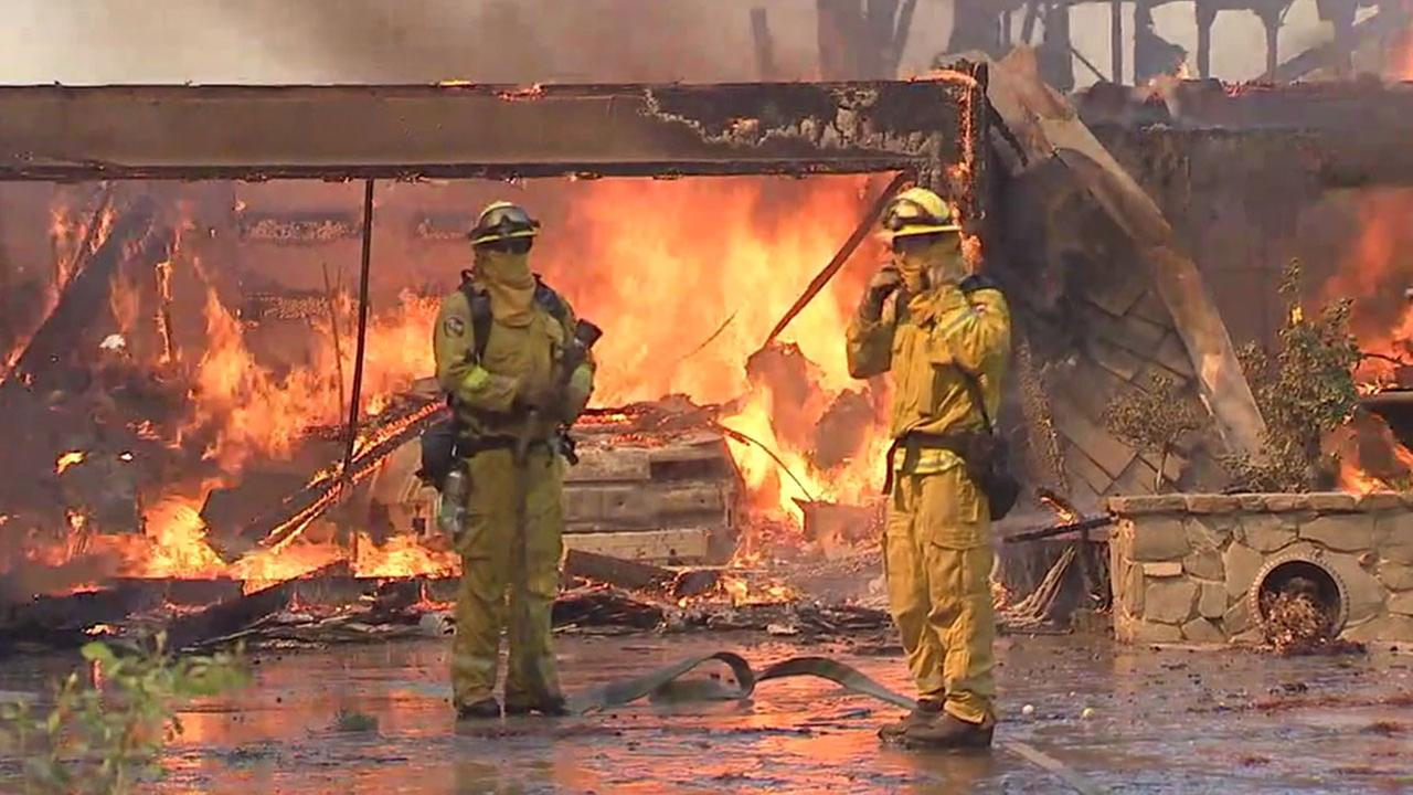 Firefighters beat back flames consuming a residence near Serrano Avenue in Anaheim Hills Monday.