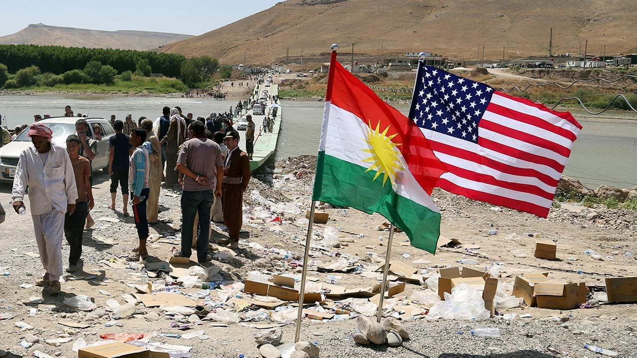U.S. and Kurdish flags flutter in the wind while displaced Iraqis from the Yazidi community cross the Syria-Iraq border in northern Iraq, Sunday, Aug. 10, 2014.