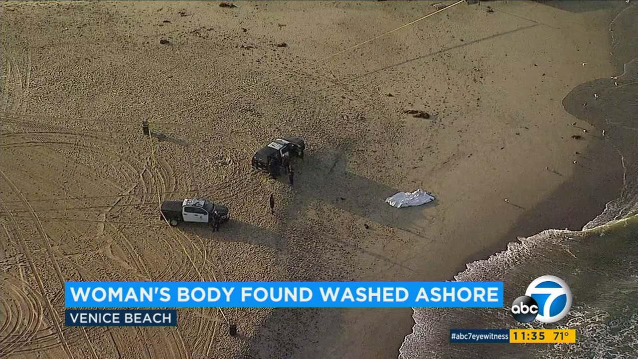 Law enforcement officials investigate the scene on Venice Beach, where a body washed ashore on Thursday, Oct. 12, 2017.