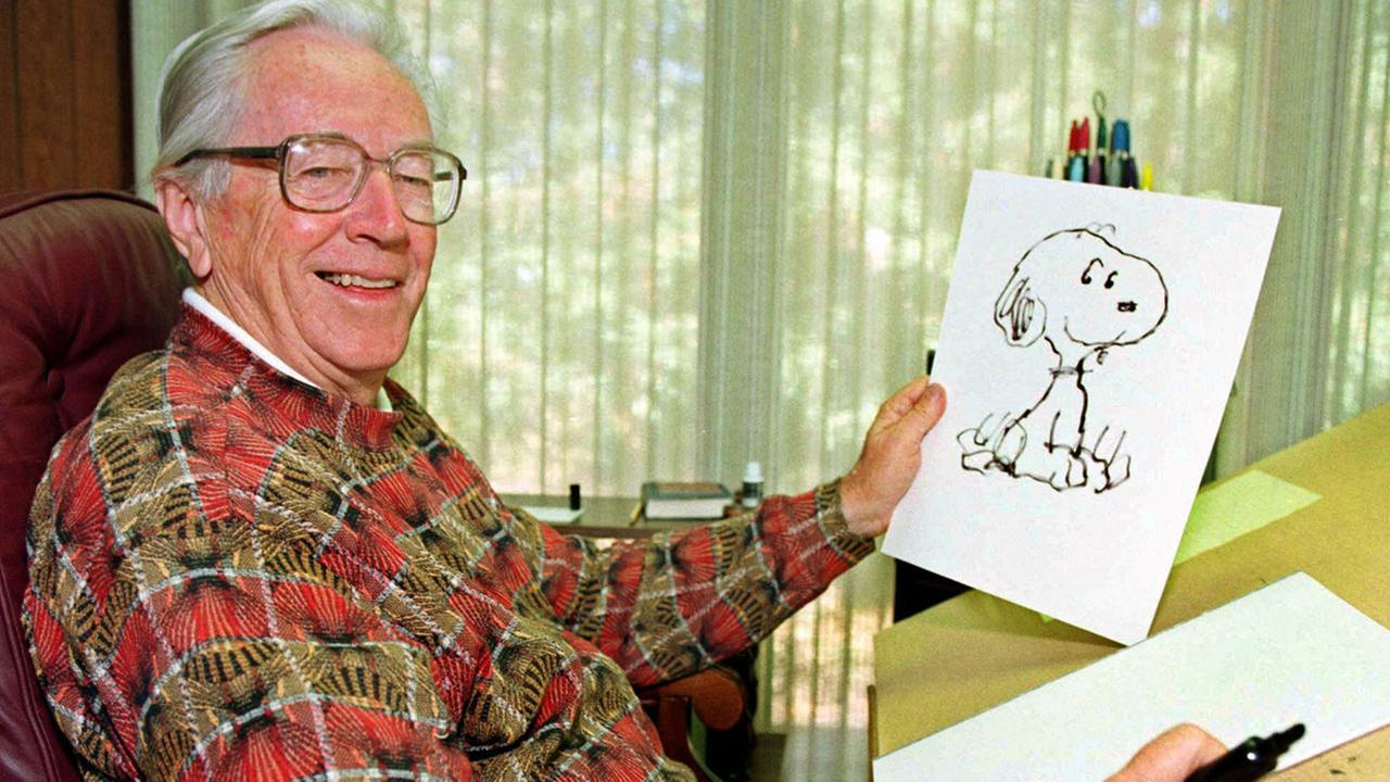 Cartoonist Charles Schulz displays a sketch of his beloved character Snoopy in his office in Santa Rosa, Calif. in 1997.