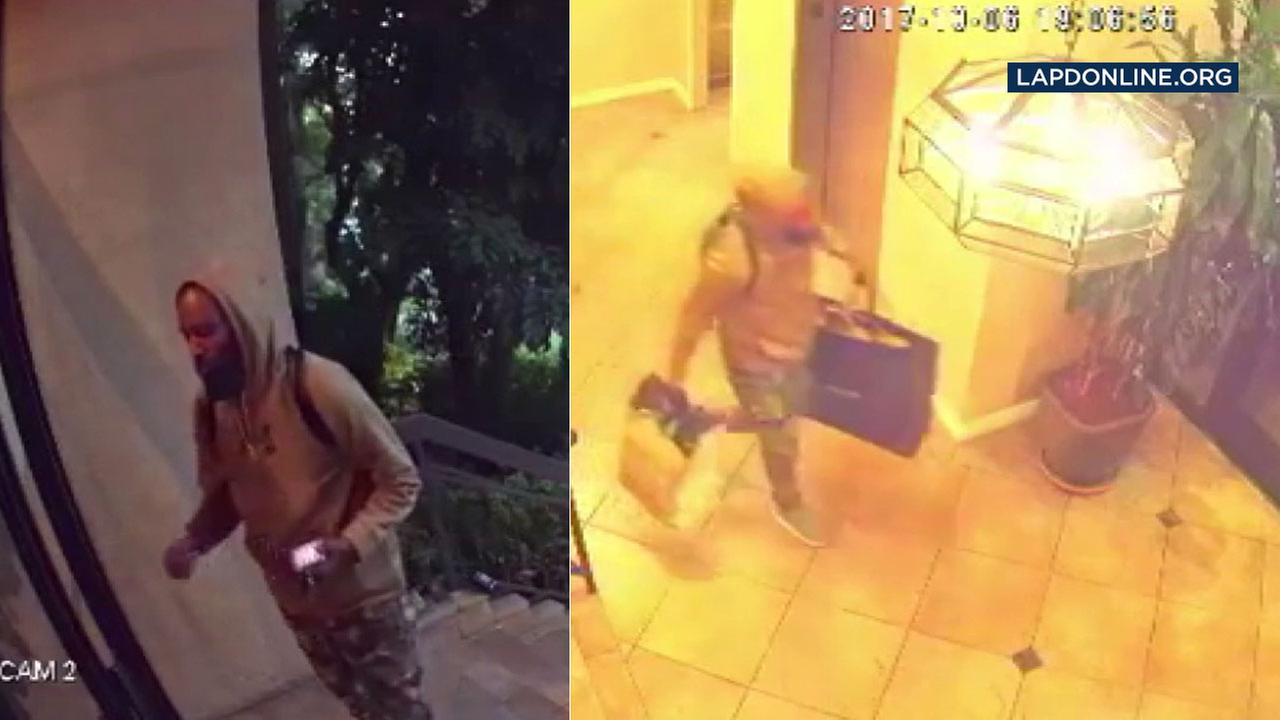 Surveillance video shows a burglary suspect loitering in front of a Hollywood apartment complex before walking out with two bags full of the victims possessions.