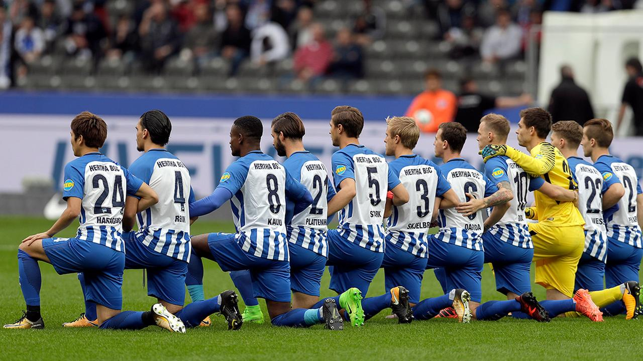 Players of Berlin kneel down prior to the German Bundesliga soccer match between Hertha BSC Berlin and FC Schalke 04 in Berlin, Germany, Saturday, Oct. 14, 2017.