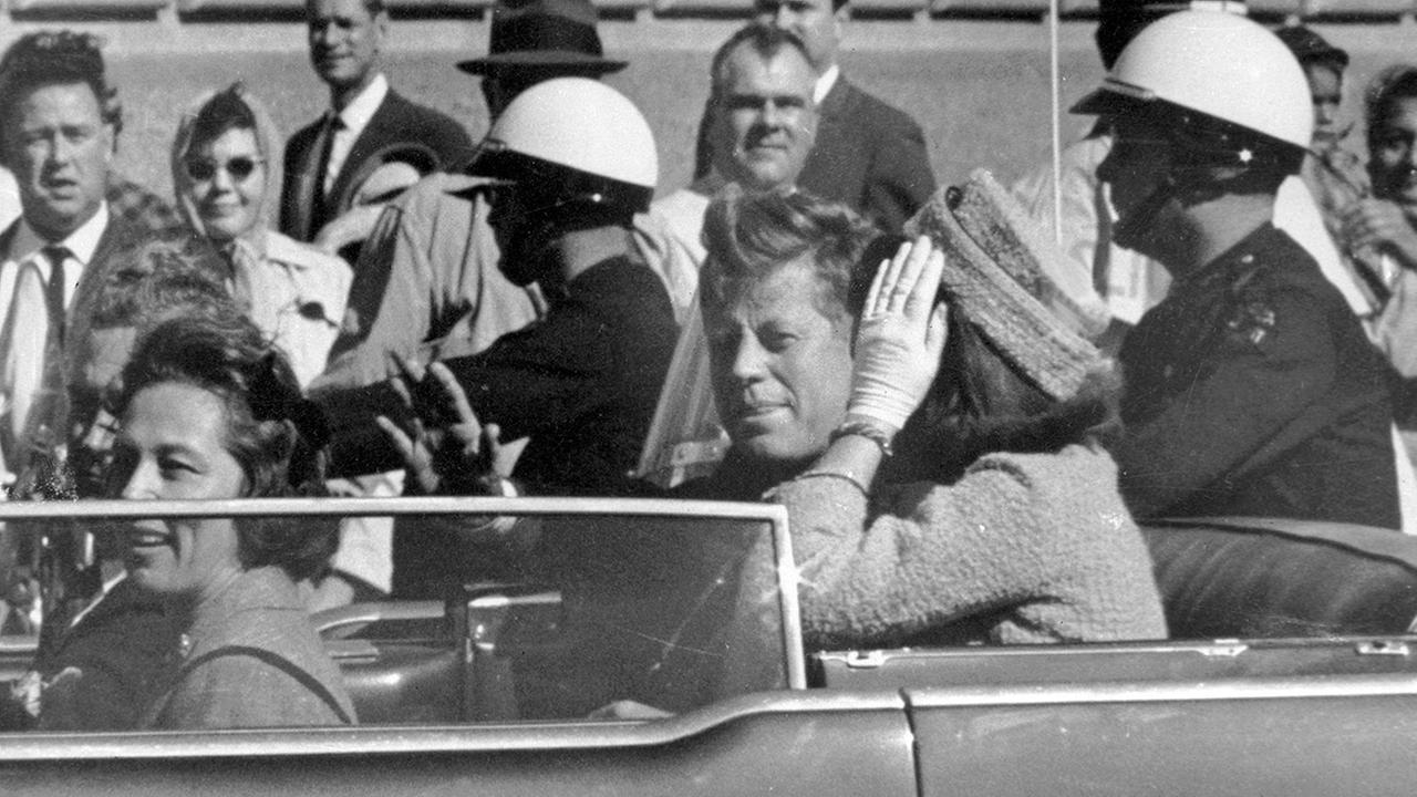 In this Nov. 22, 1963 file photo, President John F. Kennedy waves from his car in a motorcade in Dallas.