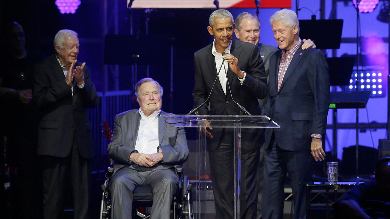Former President Barack Obama speaks as Jimmy Carter, George H.W. Bush, George W. Bush, and Bill Clinton look on during a hurricane relief concert in College Station, Texas.