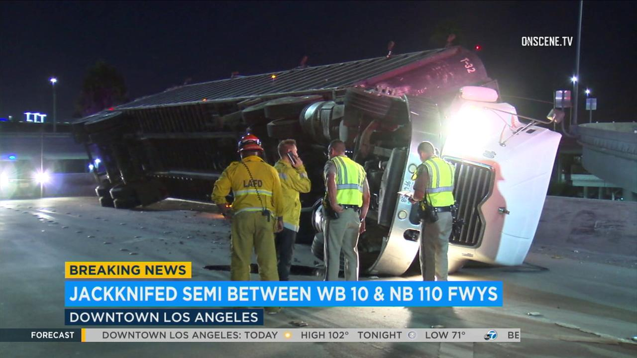 A major freeway transition road was shut down early Monday morning after a semi-truck overturned in downtown Los Angeles, officials said.