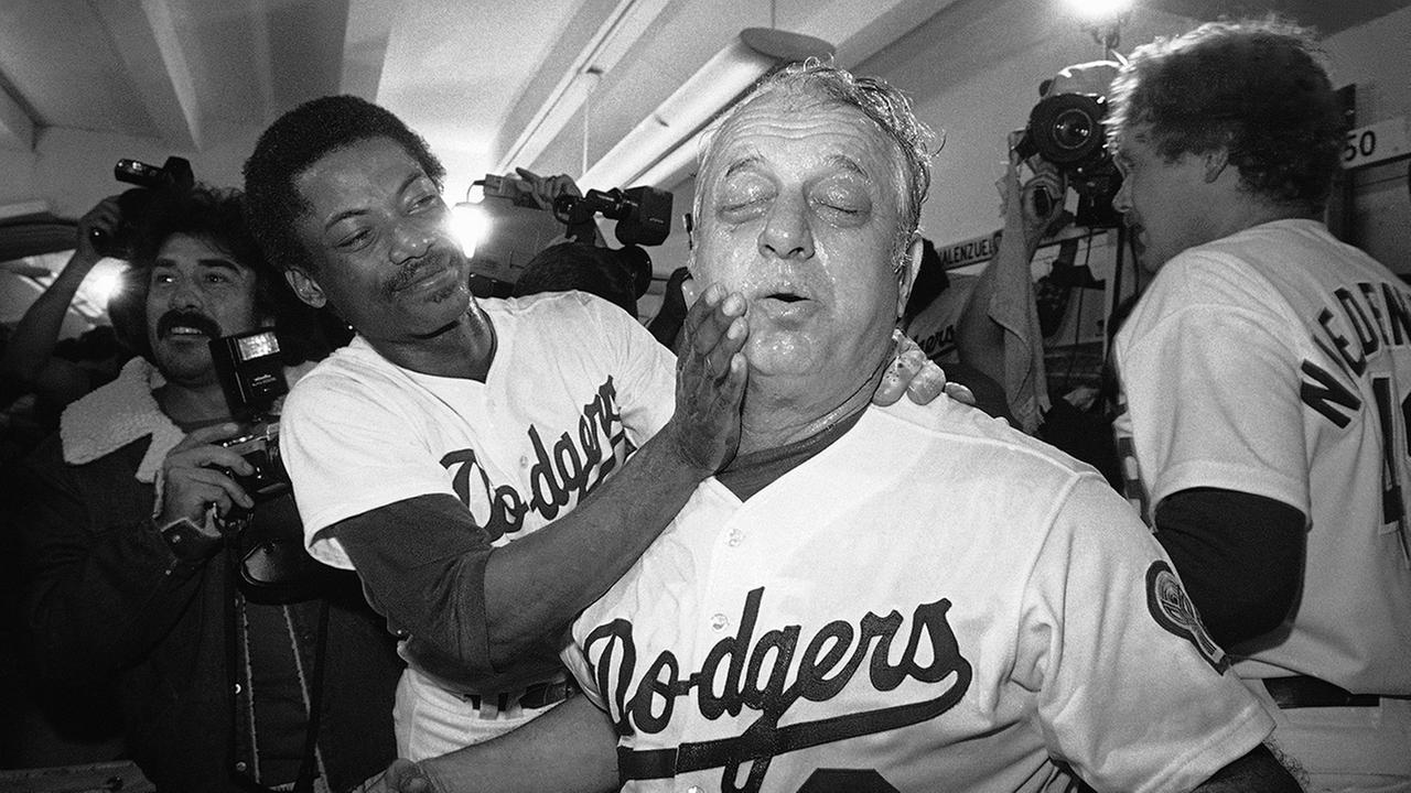 In this Oct. 11, 1981, file photo, Dodgers manager Tommy Lasorda, right, has the victory champagne rubbed into his face by Derrel Thomas after the Dodgers defeated the Astros.