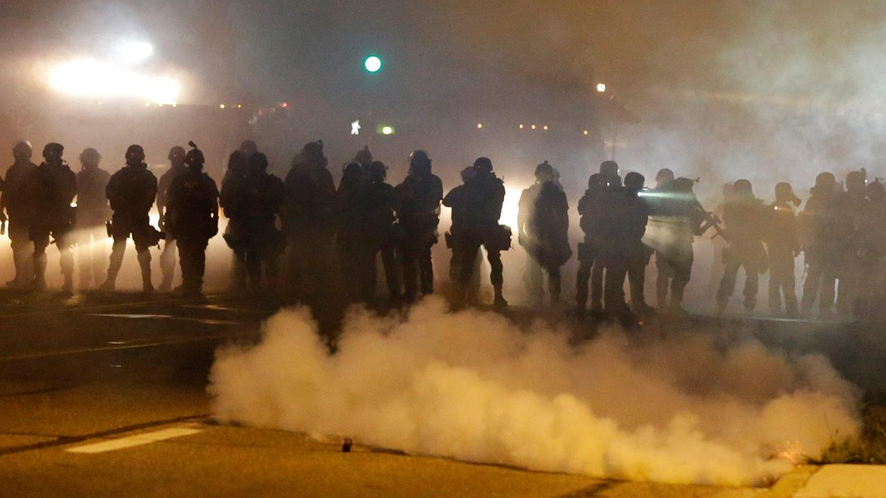 Police advance through smoke Wednesday, Aug. 13, 2014, in Ferguson, Mo.