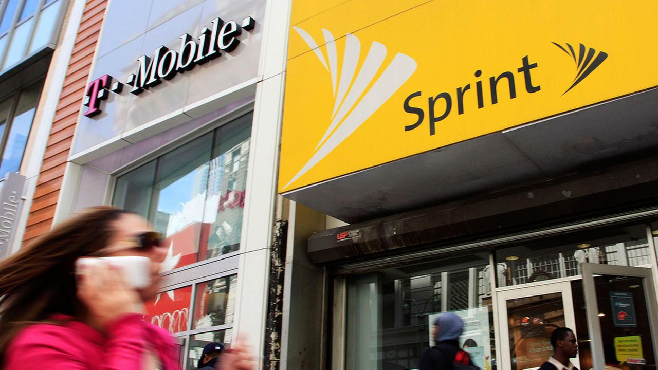 A woman using a cell phone walks past T-Mobile and Sprint stores, Tuesday, April 27, 2010, in New York.