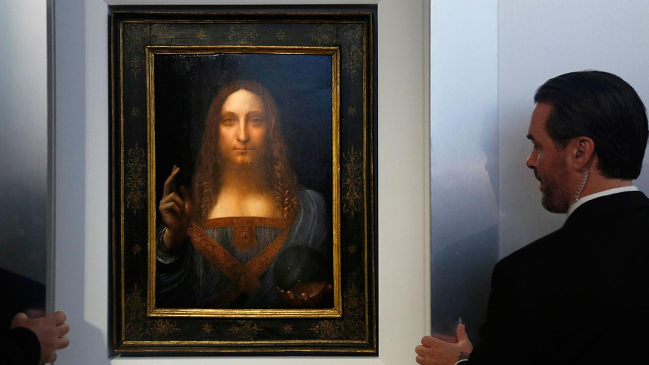 Security guards help display the painting Salvator Mundi by Leonardo da Vinci at Christies New York on Oct. 10, 2017.