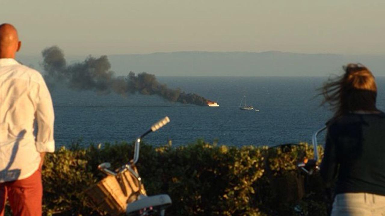 Bystanders watch a boat burn off the coast of Malibu on Saturday, Aug. 16, 2014.