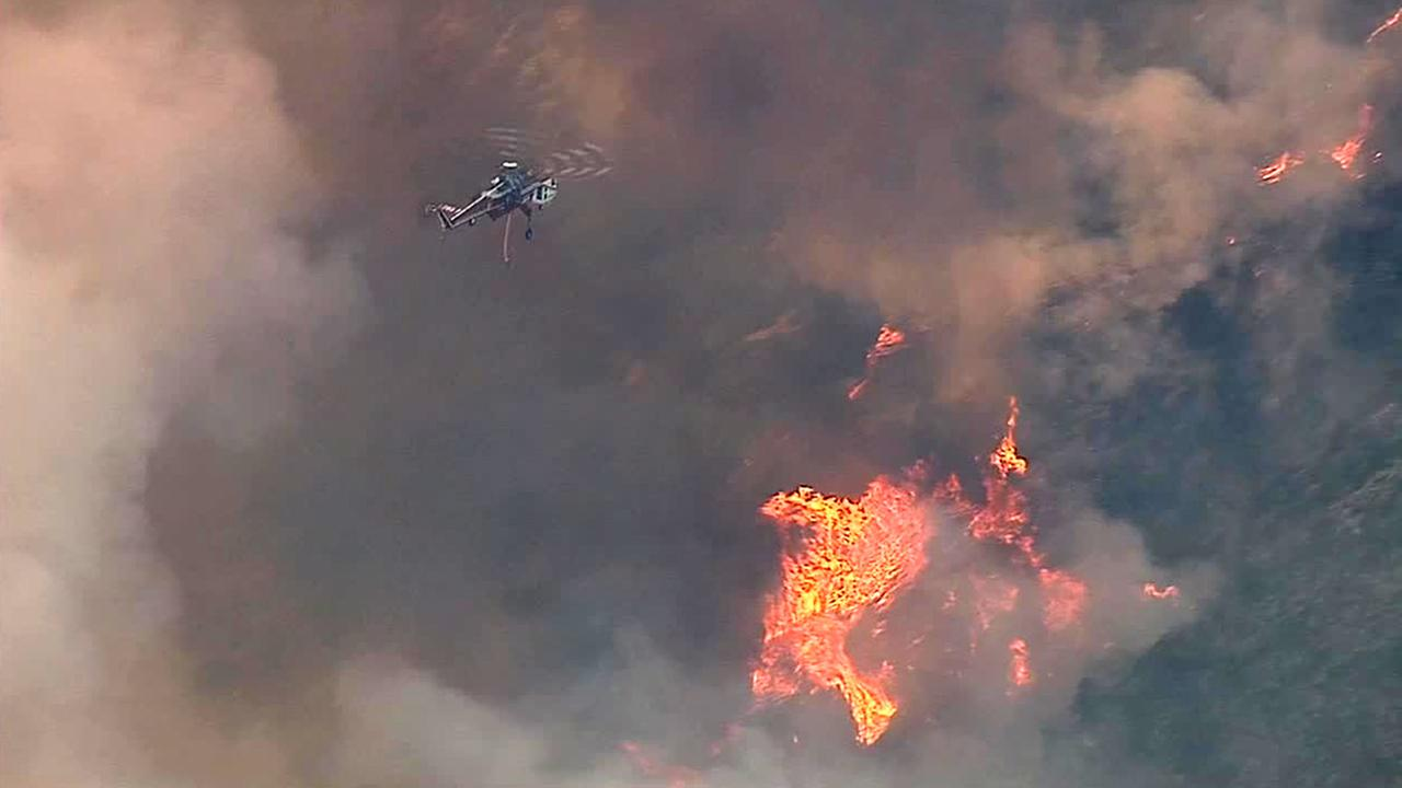 A helicopter flies through smoke and towards flames in the Angeles National Forest on Sunday, Aug. 17, 2014.