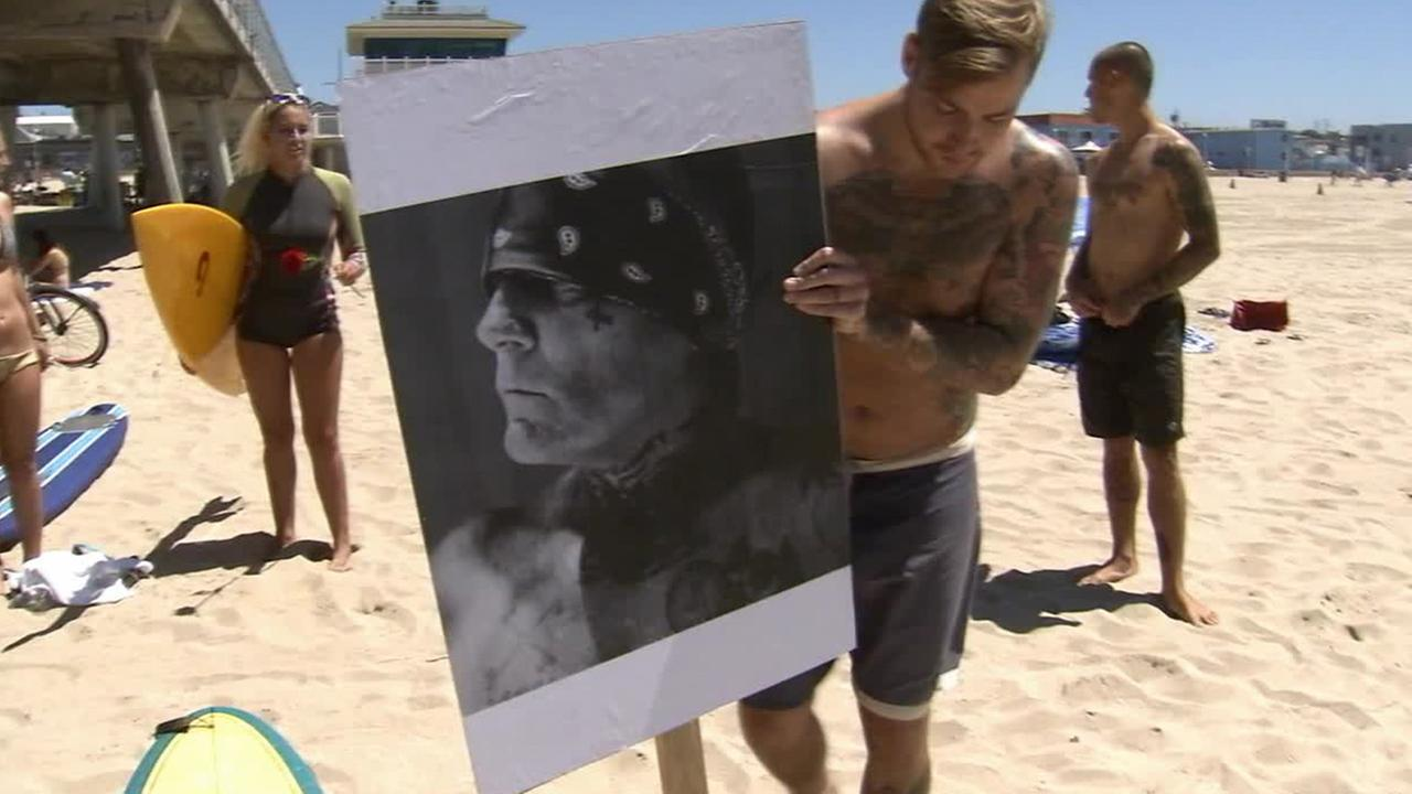 A man holds up a photo of Jay Adams at Hermosa Beach on Sunday, Aug. 17, 2014.