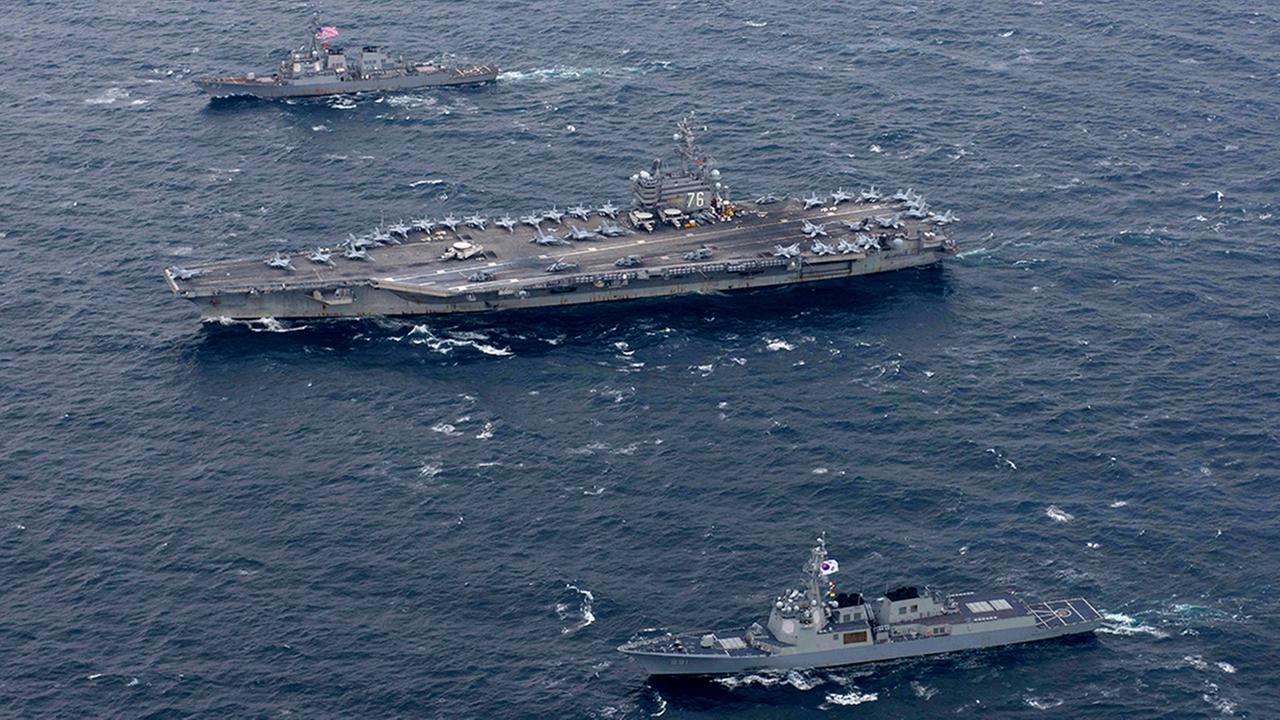 The Navys aircraft carrier USS Ronald Reagan, center, and the forward-deployed Arleigh Burke-class destroyer USS Stethem, left, steam alongside ships from the South Korean navy.