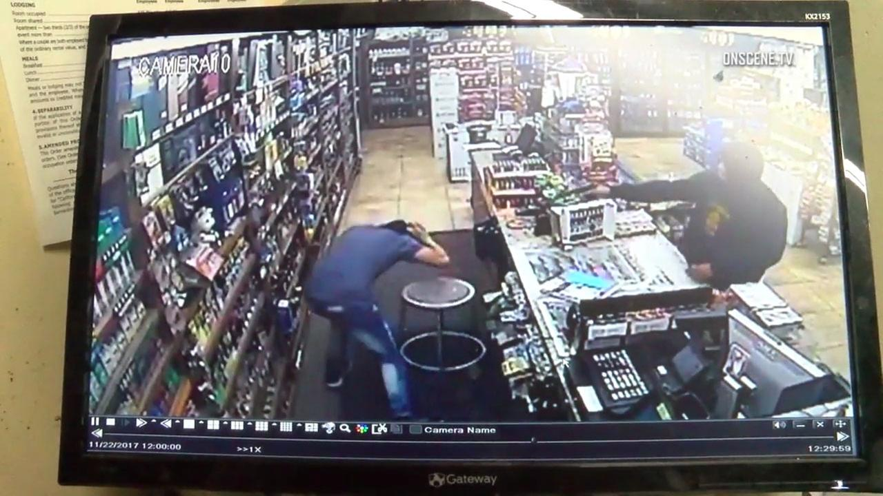 Surveillance video shows an armed suspect demanding cash at a Santa Ana liquor store around midnight on Wednesday, Nov. 22, 2017.