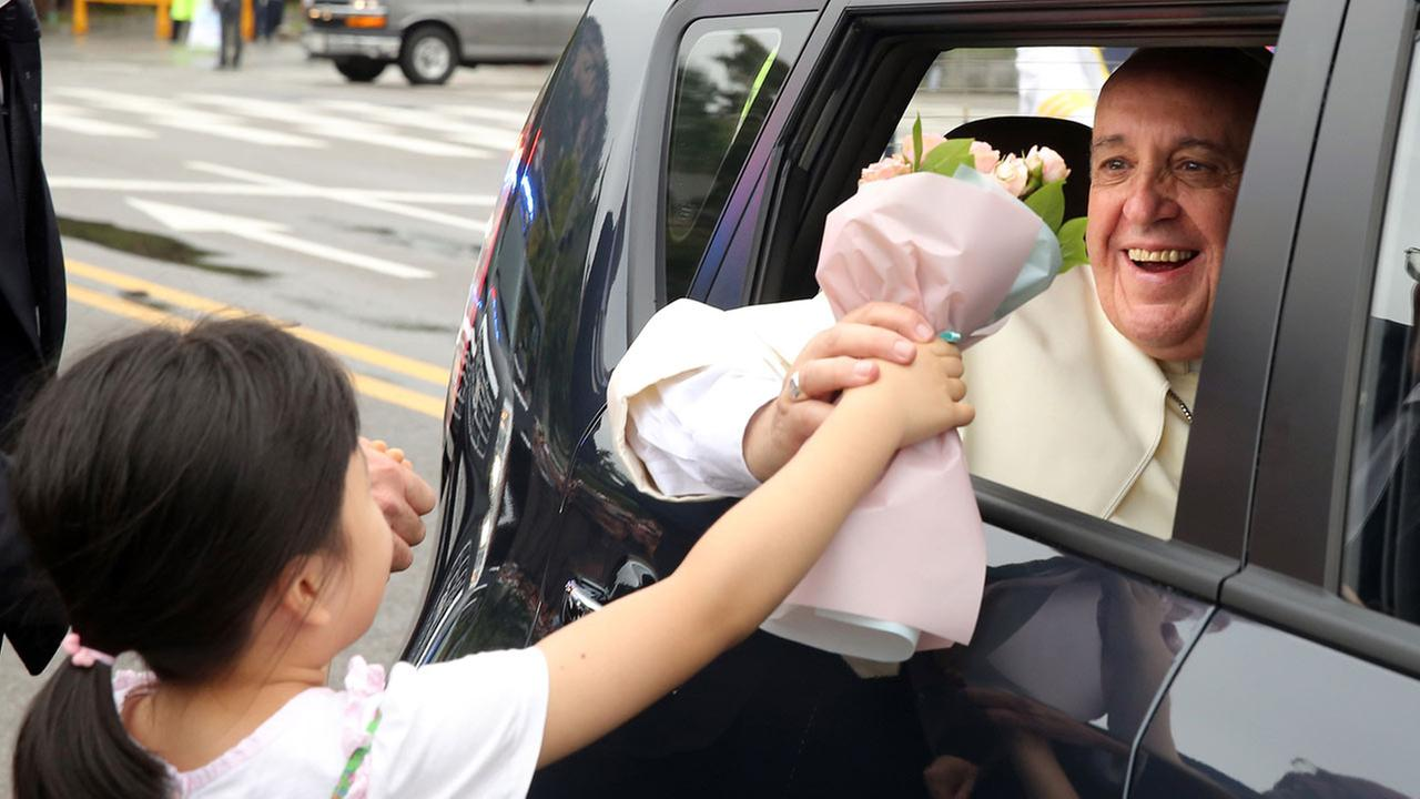 Pope Francis receives a bouquet of flowers from a child as he leaves in a car in Seoul at the end of his five-day visit to South Korea, Monday, Aug. 18, 2014.