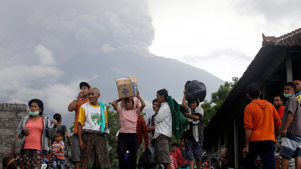 Villagers carry their belongings during an evacuation following the eruption of Mount Agung, seen in the background, in Karangasem, Indonesia, Sunday, Nov. 26, 2017.