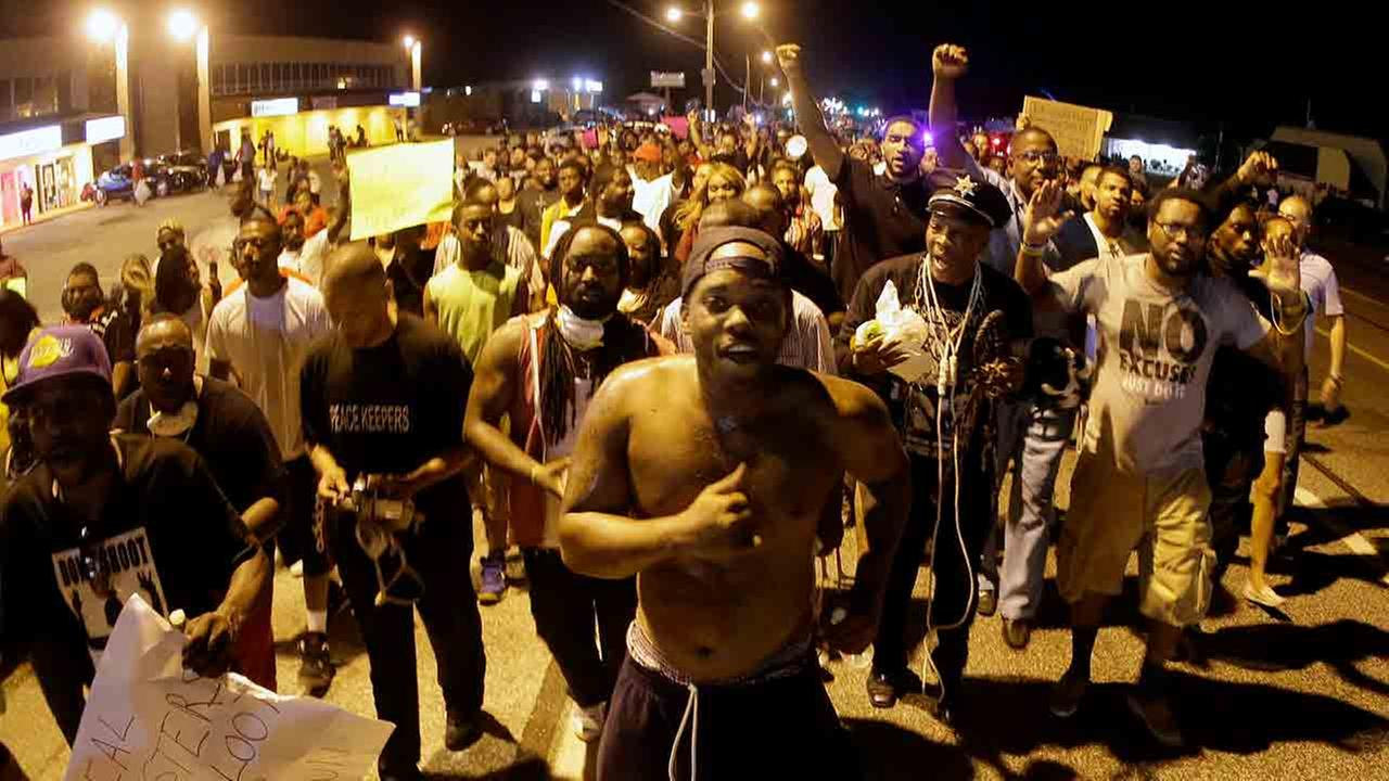 People march Tuesday, Aug. 19, 2014, during a rally for Michael Brown, who was killed by police Aug. 9 in Ferguson, Mo.