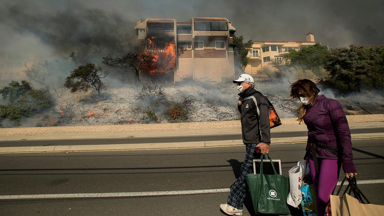 James and Josie Ralstin carry belongings from their Ventura, Calif., home as flames from a wildfire consume another residence on Tuesday, Dec. 5, 2017.