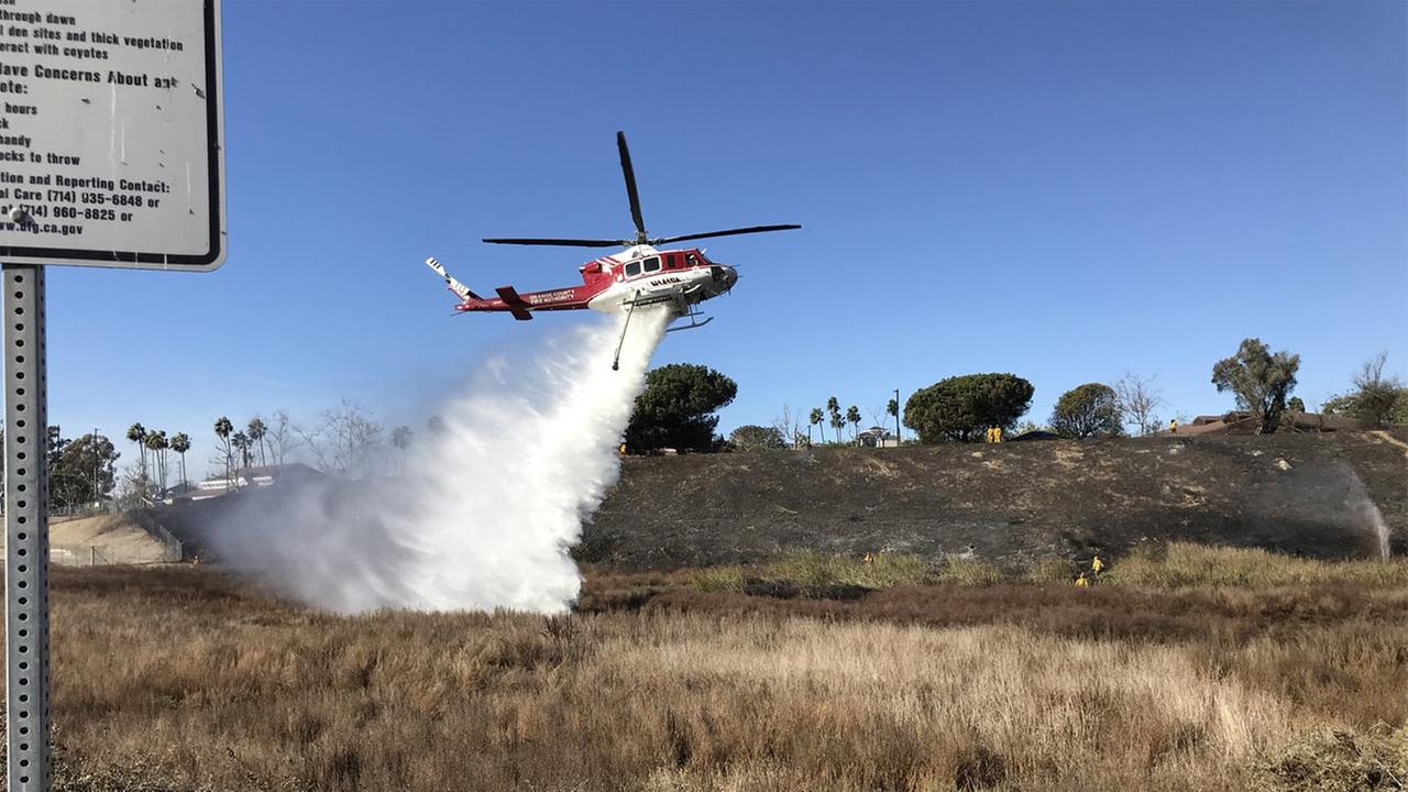 'Fire crews respond to a brush fire in Huntington Beach on Thursday, Dec. 7, 2017.' from the web at 'http://cdn.abclocal.go.com/content/kabc/images/cms/2752724_1280x720.jpg'